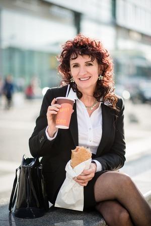 negocios comida: Superior de la mujer de negocios en el almuerzo de comida rápida - potable para llevar el café y comiendo sándwich en la calle