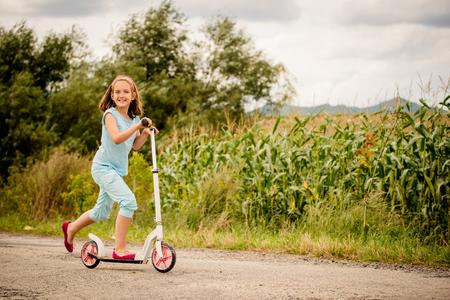 Mooi meisje scooter rijden op landelijke weg outdor in de natuur