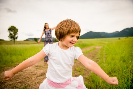 authentic: Mother and child having fun and dancing outdoor in nature Stock Photo