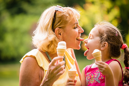 grandmother: Grandmother licking icecream from nose of her grandchild outdoor in nature Stock Photo