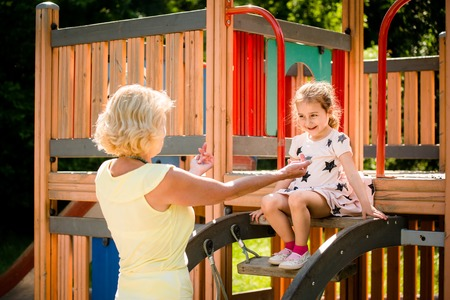 granddaughter: Authentic photo of grandmother helping her grandchild in playground
