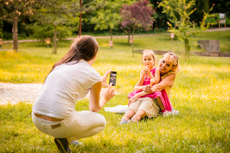 authentic: Mother taking photo of her child with grandmother eating icecream outdoor in park Stock Photo