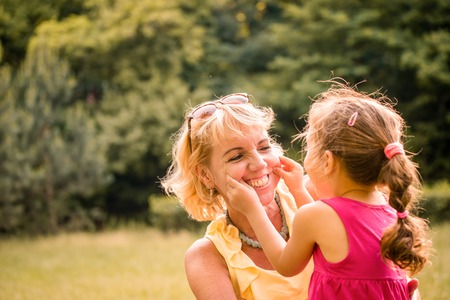 nature photo: Authentic photo of grandmother and her grandchild playing together and having fun outdoor in nature