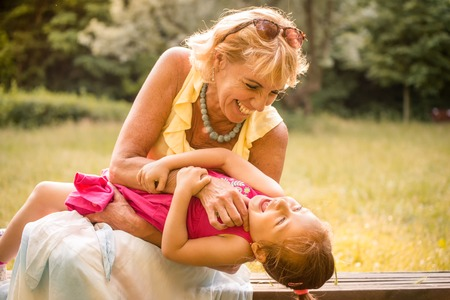 authentic: Authentic photo of grandmother and her grandchild playing together and having fun outdoor in nature