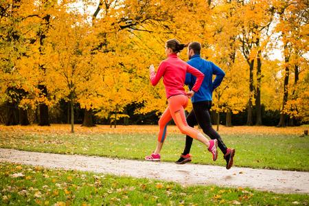 gente corriendo: Pareja joven trotar junto en parque - temporada de otoño Foto de archivo