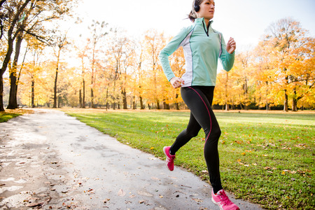 listening: Young woman with headphones  jogging in fall nature and listening music