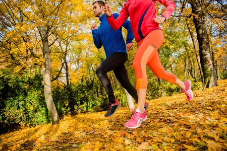 hacer footing: Detalle de la pareja trotar juntos en la naturaleza hermosa del otoño