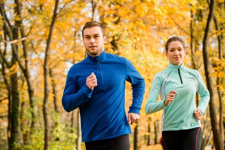Joggen paar - jonge man en vrouw concurreren, man eerst Stockfoto