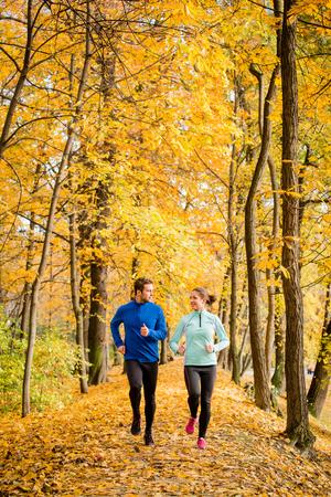 personas trotando: Joven pareja hablando, salir a correr juntos en la naturaleza hermosa del otoño