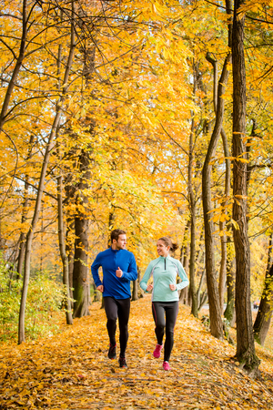 active woman: Young couple talking while jogging together in beautiful autumn nature Stock Photo