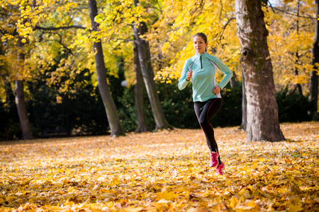 Young woman jogging and training in autumn nature