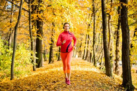 Jonge vrouw met een hoofdtelefoon joggen in het najaar de natuur en het luisteren muziek