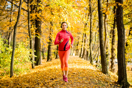 Young woman with headphones  jogging in autumn nature and listening music