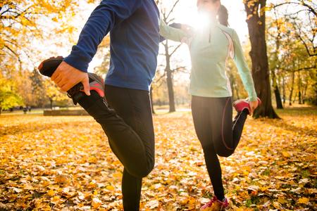 フィットネス: 男と女の秋の自然の中をジョギングする前に足をストレッチの詳細 写真素材