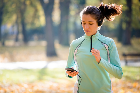 秋の自然の中をジョギングと携帯電話をヘッドフォンを持つ若い女性