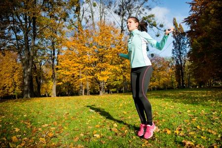 Workout - jonge vrouw springen met springtouw