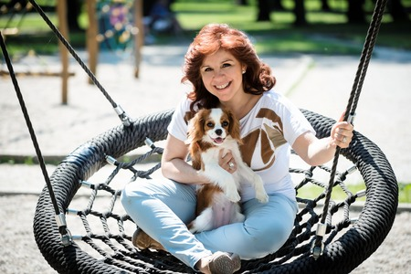 cavalier: Mature woman swing with her cavalier dog outdoor in playground