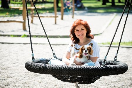 animal woman: Mature woman swinging with her animal friend outside in playground Stock Photo