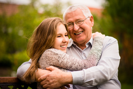 Happy grandfather hugging with his teenage granddaughter outdoor in nature Stock Photo