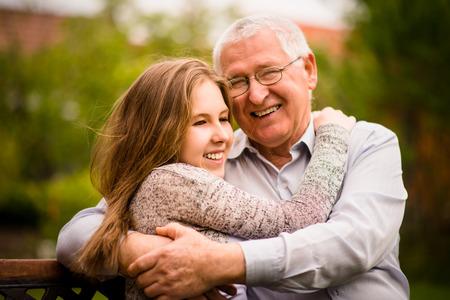 uomo felice: Nonno felice che abbraccia con il suo adolescente all'aperto nipote nella natura Archivio Fotografico