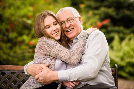 彼の 10 代の孫娘の屋外自然の中で抱いて笑顔の祖父の本格的な写真 写真素材