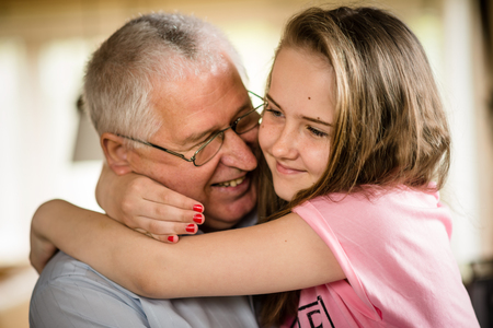 authentic: Authentic photo of happy grandfather hugging with his granddaughter indoor at home