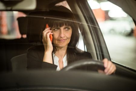 front view: Detail of senior business woman calling mobile phone while driving car at night - view through front window
