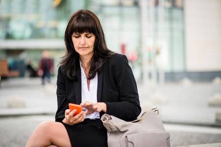 mature woman: Senior business woman looking to her mobile phone standing in street