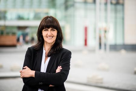 Portrait of smiling confident senior business woman in a street Standard-Bild