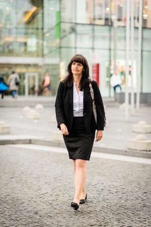 falda: mujer de negocios de alto nivel a pie de calle, edificios modernos en el fondo