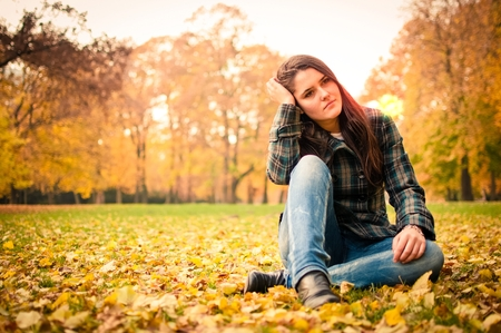 Young woman in depression outdoor in autumn nature Stock Photo