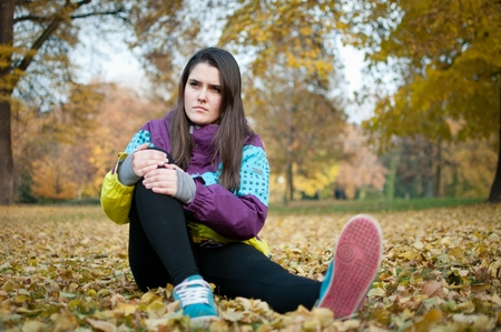 sitting on the ground: Sport injury - young fitness woman holding her knee with pain outdoor sitting on ground Stock Photo