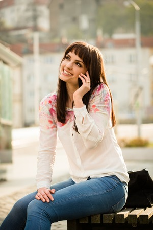 women in jeans: Authentic photo of young woman calling phone - sitting on bench in street
