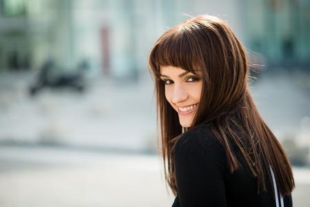 Authentiek portret van glimlachende vrouw lturning en kijken over de schouder Stockfoto