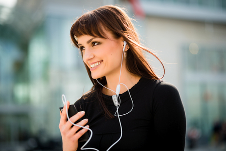 hands free: Young woman calling phone with hands free in street