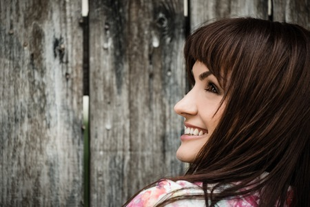 Profile portrait of  young smiling woman looking over her shoulder on wooden fence background