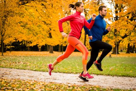 people jogging: Pareja joven trotar junto en parque - visión trasera