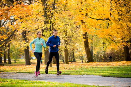 jogging in nature: Young couple jogging together in park - autumn season