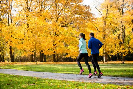 personas corriendo: Pareja joven trotar junto en parque - visión trasera