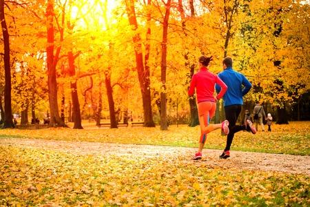 personas corriendo: Pareja joven corriendo juntos en parque - caer la naturaleza