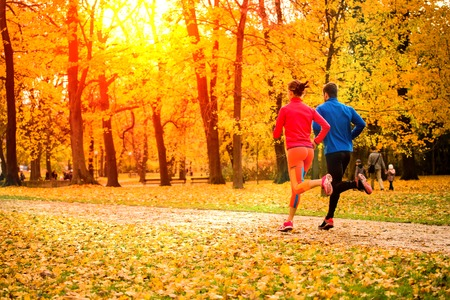 a workout: Young couple running together in park - fall nature Stock Photo