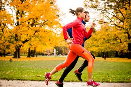 hacer footing: Pareja joven trotar junto en parque - visión trasera