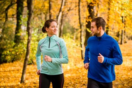 hacer footing: Joven pareja hablando, salir a correr juntos en la naturaleza hermosa del otoño