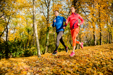 healthy men: Young couple jogging together in fallen autumn leaves