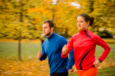 jogging: Panning photo of young couple jogging together in nature Stock Photo