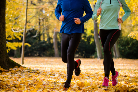 jogging: Detail of couple jogging together in beautiful autumn nature