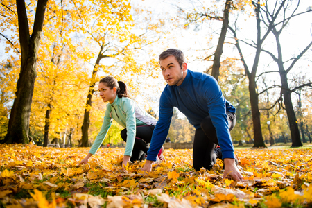 rival rivals rivalry season: Young couple in starting position prepared for running in autumn nature