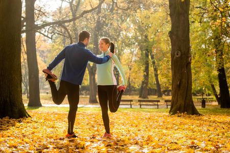 hacer footing: Pareja joven que estira las piernas antes de trotar en la naturaleza del otoño