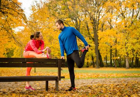 estiramiento: Pareja joven que estira los músculos en el banco antes de correr en la naturaleza del otoño