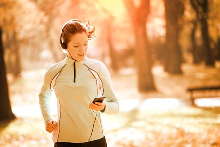Jonge vrouw met een hoofdtelefoon joggen in het najaar de natuur en op zoek naar de mobiele telefoon